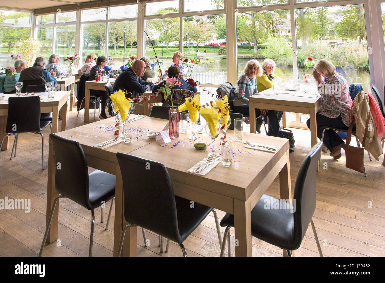 Restuarant interior; Customers; Relaxed atmosphere; Enjoying; Enjoyment; Reserved table; Celebration; Table decorations; - Stock Image