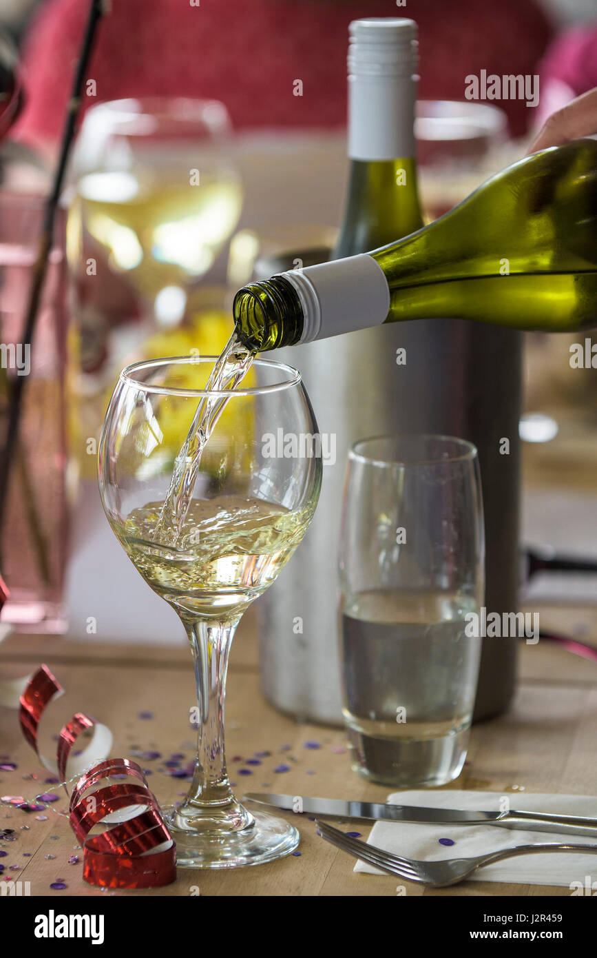 White wine poured into a glass Alcohol Pouring Wine glass Alcohol consumption Drinking wine Dining - Stock Image