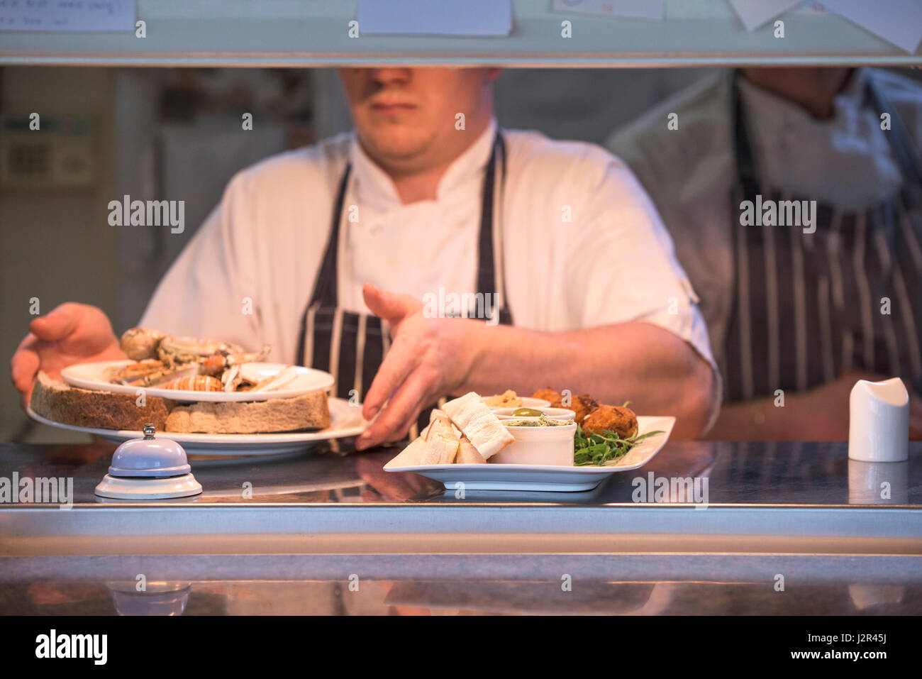 Restaurant Plates of food Serving hatch Food preparation Chef Meals Dining Food service industry Dishes - Stock Image