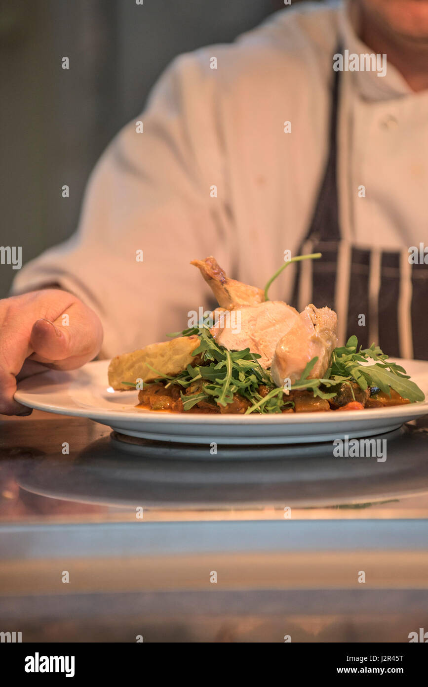 A meal prepared by a chef presented at the pass ready for serving. - Stock Image