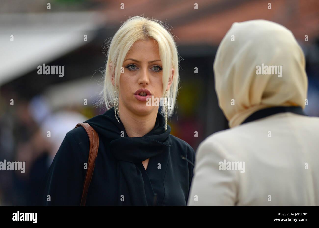 A blonde girl talks to her muslim friend Stock Photo