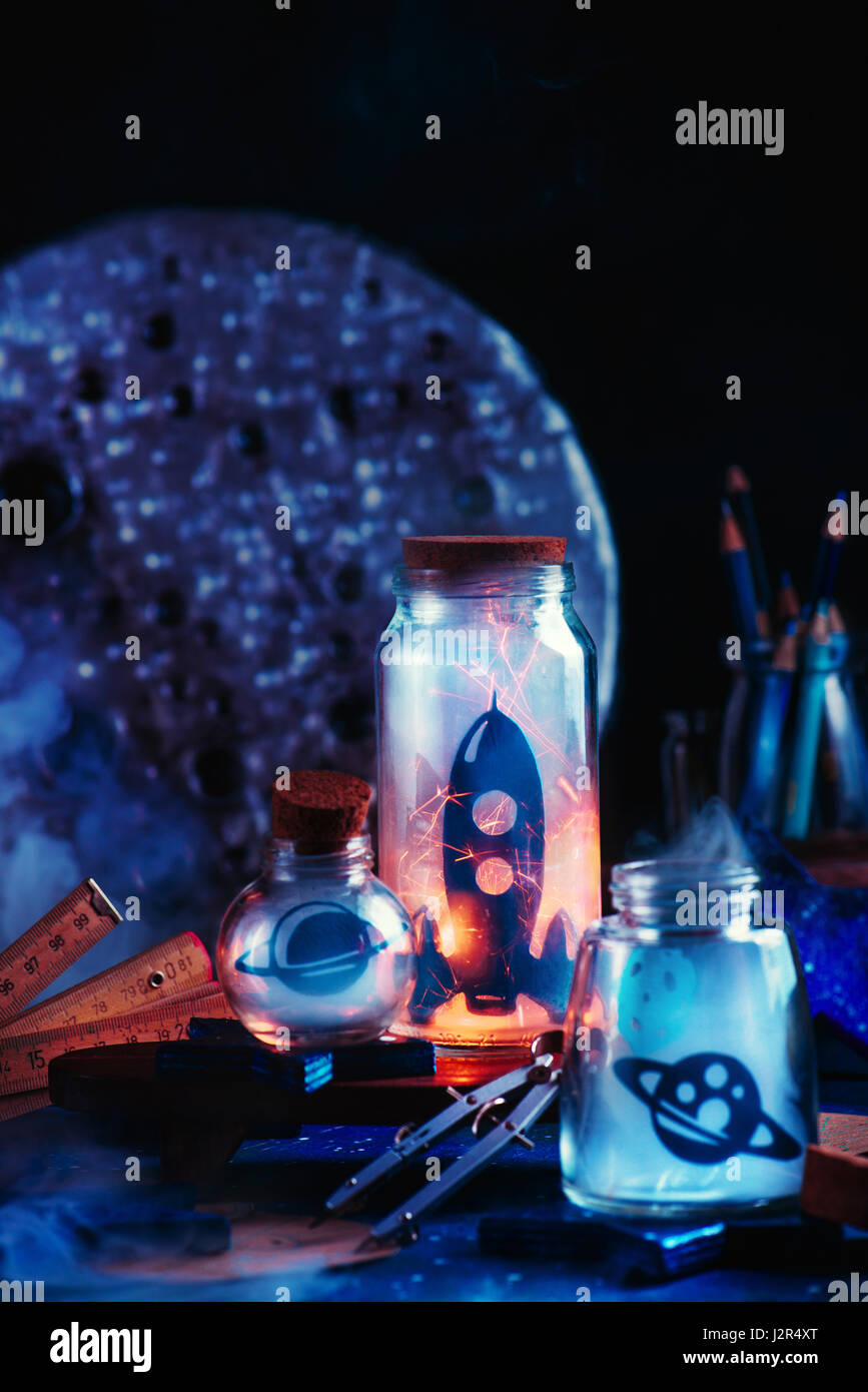 Space themed still life with rocket, planets and asteroid inside jars on a dark background - Stock Image