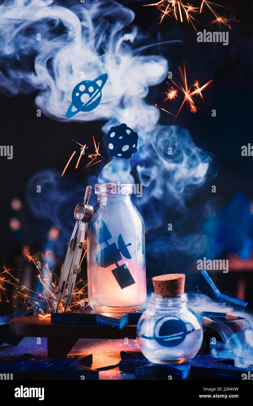 Astronomy themed still life with space station, planets and asteroid inside jars on a dark background - Stock Image