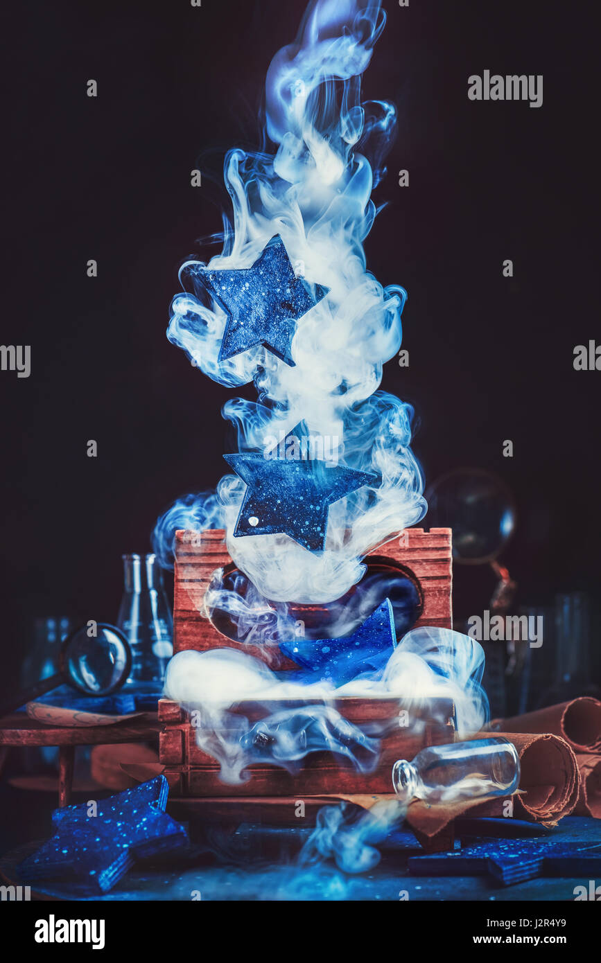 Magical wooden chest with rising stars and smoke on a dark background - Stock Image
