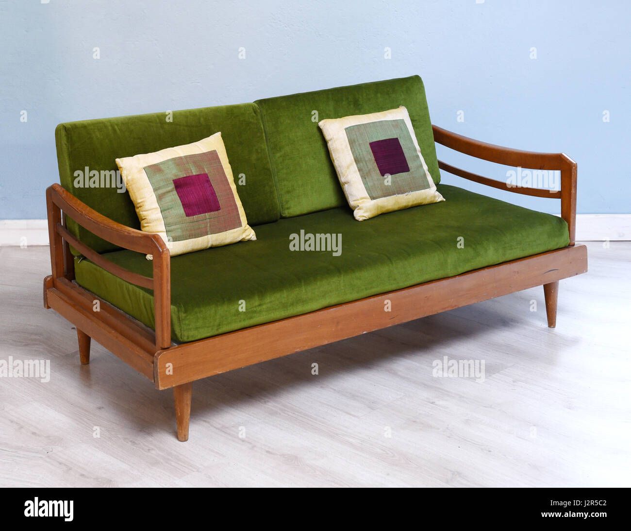 Antique upholstered settee in green with cushions in modern room - Stock Image