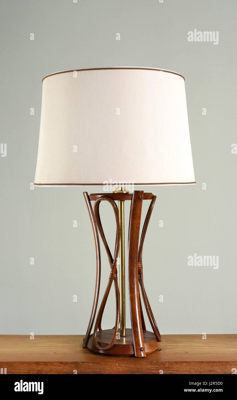 Design vintage lamp with wooden base, metal decorative leg and white fabric shade, close-up on wooden shelf against - Stock Image