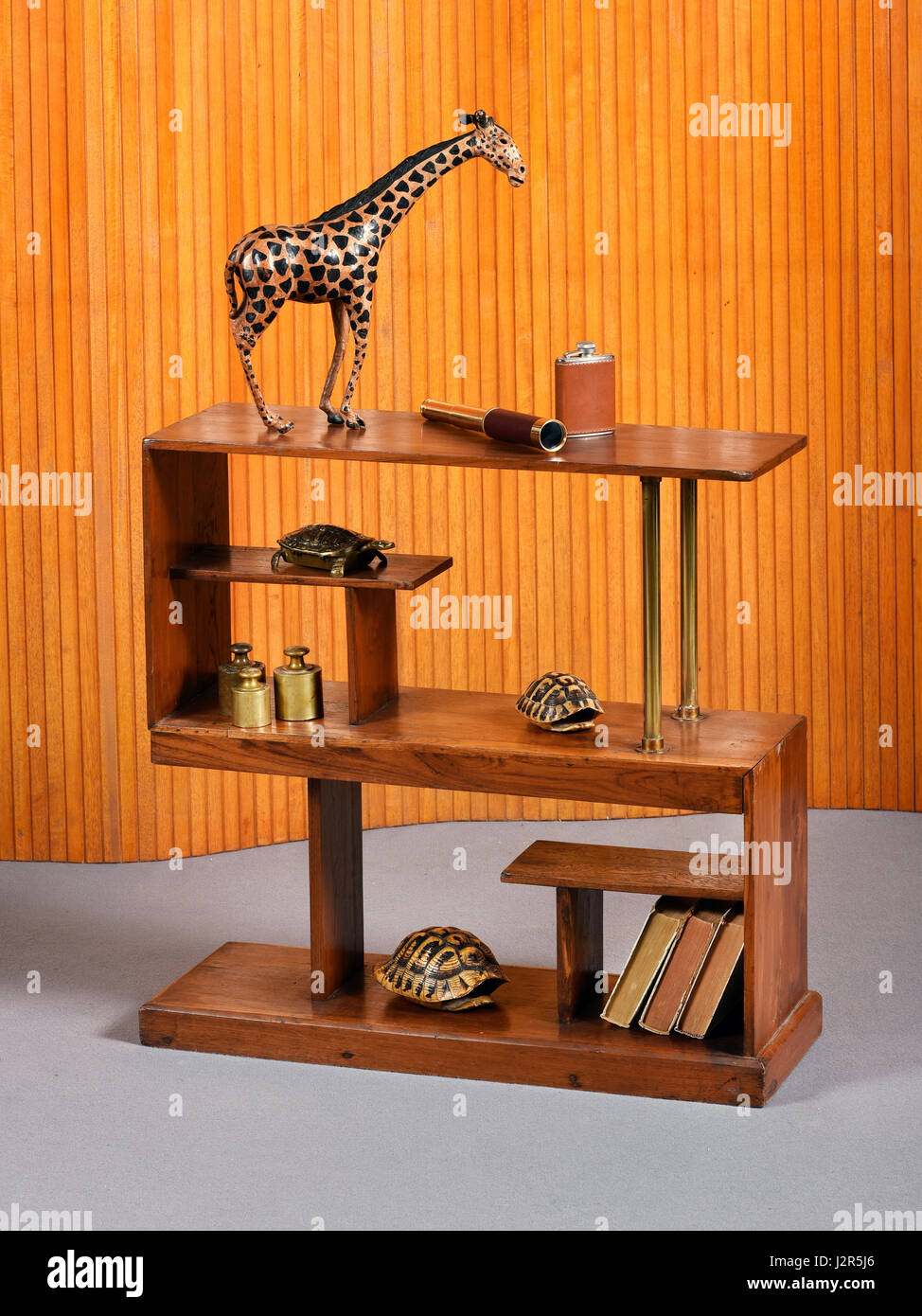Small freestanding rectangular wooden bookcase or etagere with a souvenir wooden giraffe, books tortoiseshells and - Stock Image