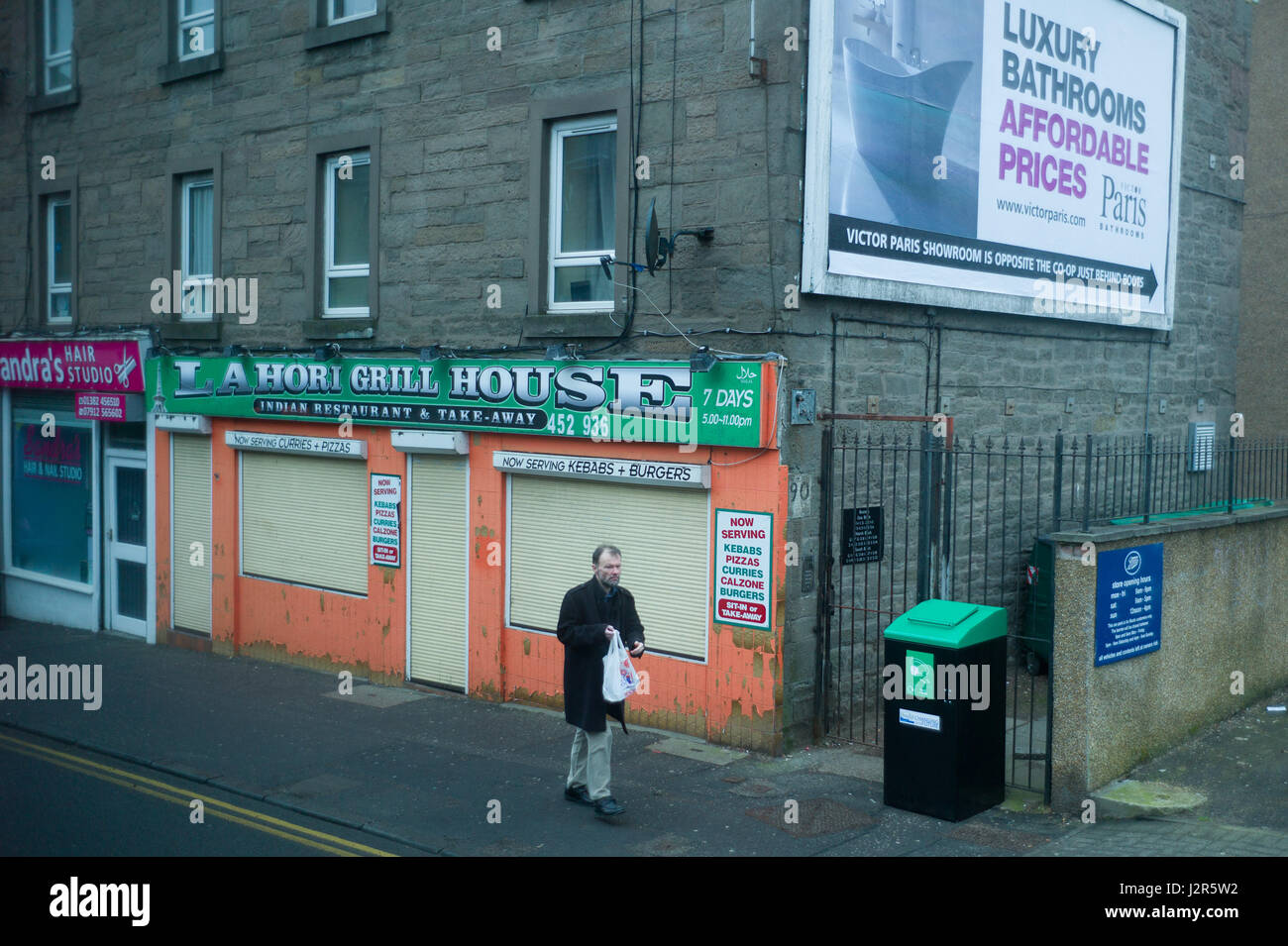 Man walks past a closed down shop in Forfar rodad a run down area of Dundee Scotland - Stock Image