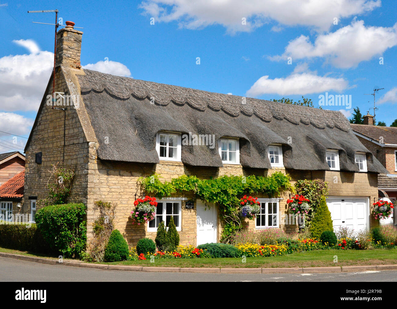 Traditional English thatched cottage with colourful garden - Stock Image