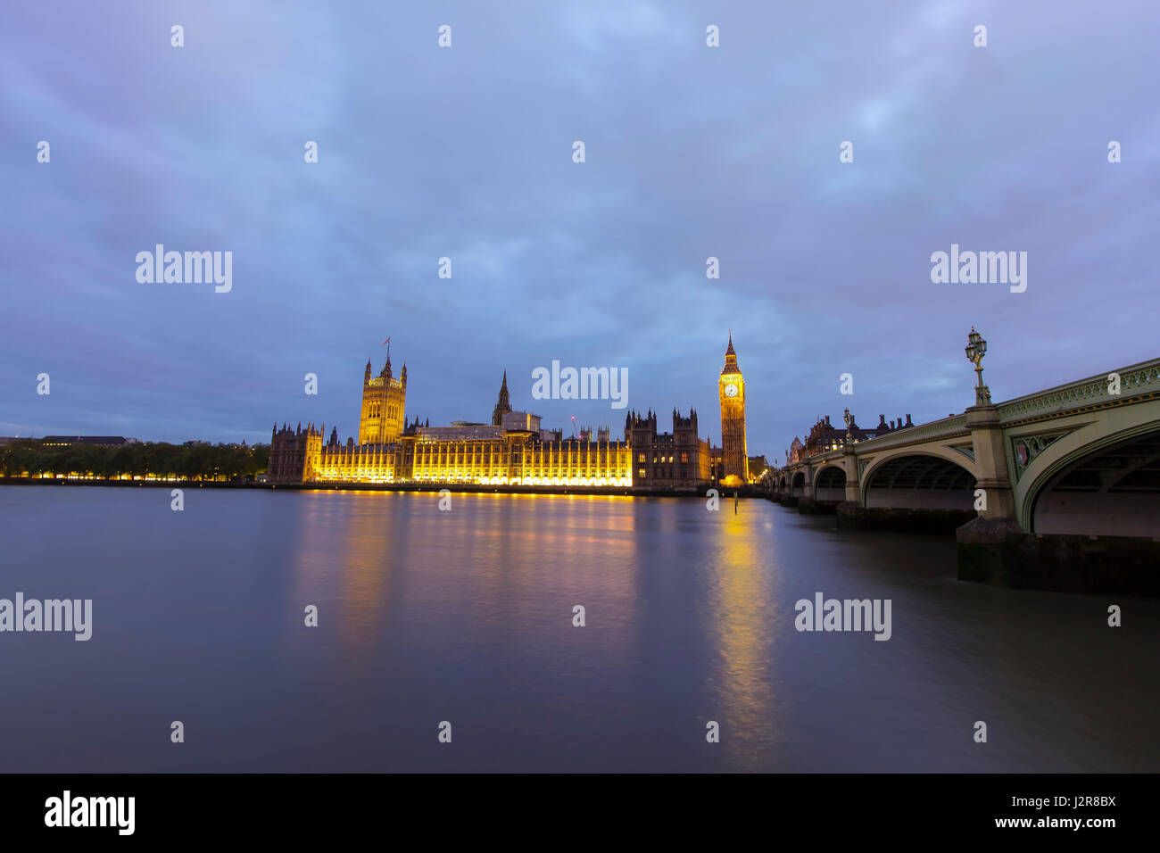 View of the tower of Big Ben and parliament buildings across the Thames river in Westminster, London. Photo taken - Stock Image