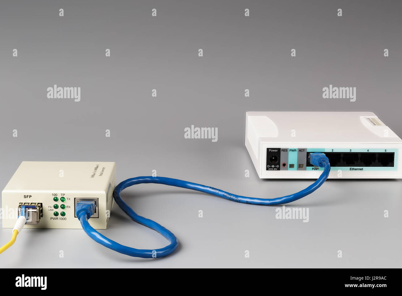 Media converter with optical patchcord and router connected via copper cable - Stock Image