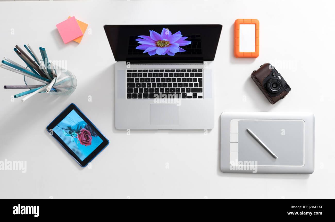 Modern digital artist's workspace comprising laptop computer, pen tablet, ipad, camera and hard disk - Stock Image