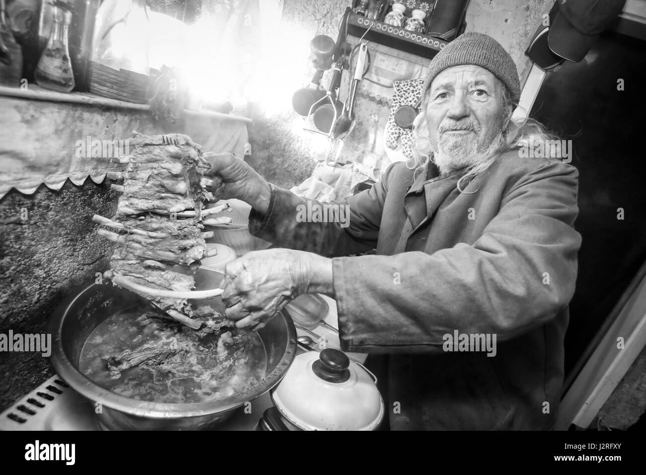 An old man boiling pork meat on the stove and holding a piece of ribs. - Stock Image