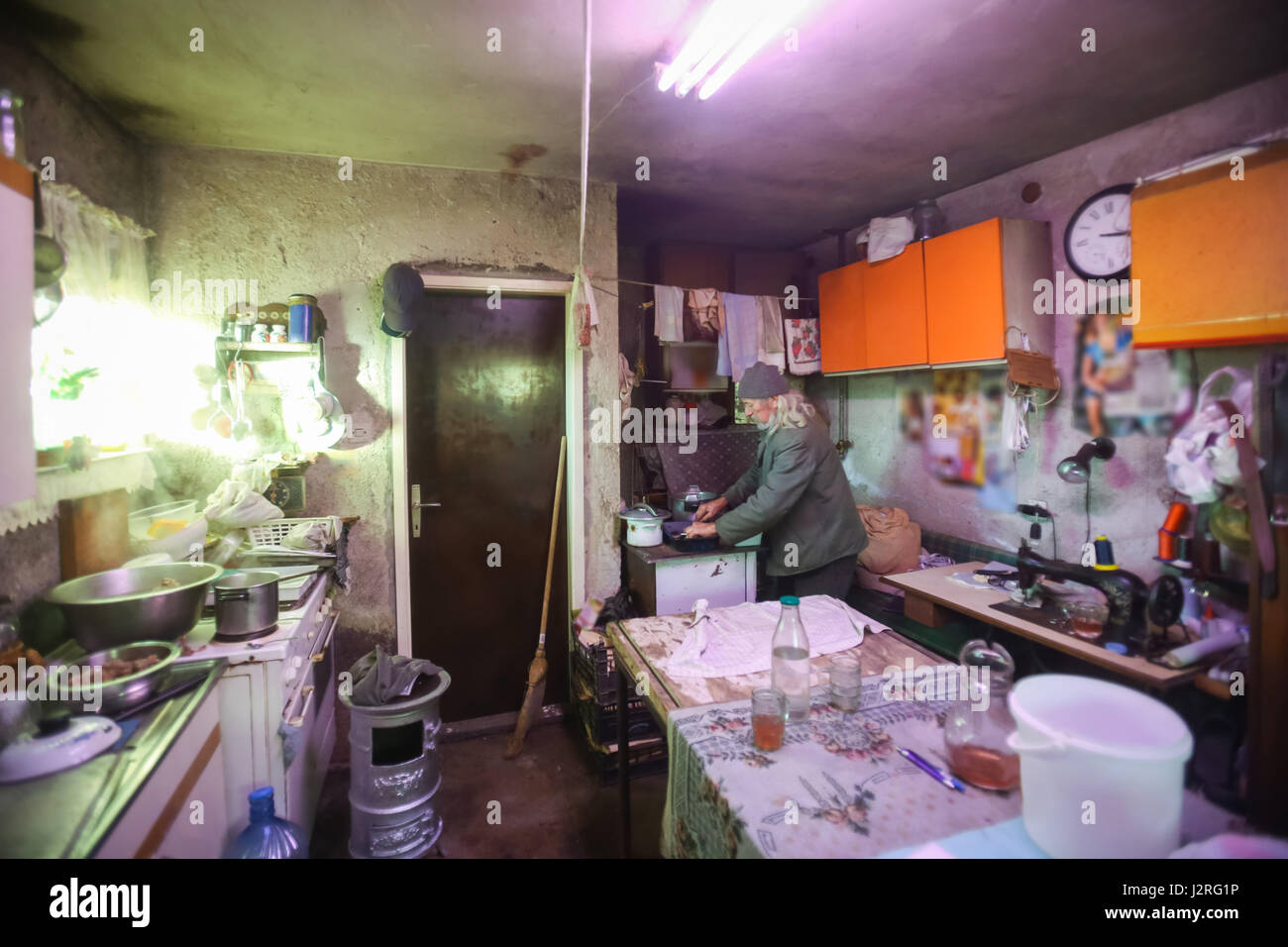 An old man cooking on the stove in an obsolete rustic kitchen. - Stock Image