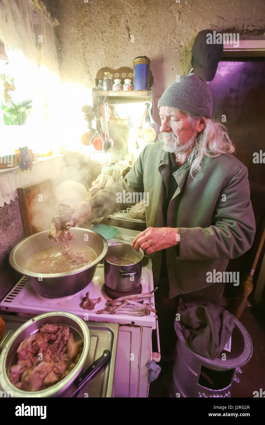 An old man boiling pork meat on the stove. - Stock Image