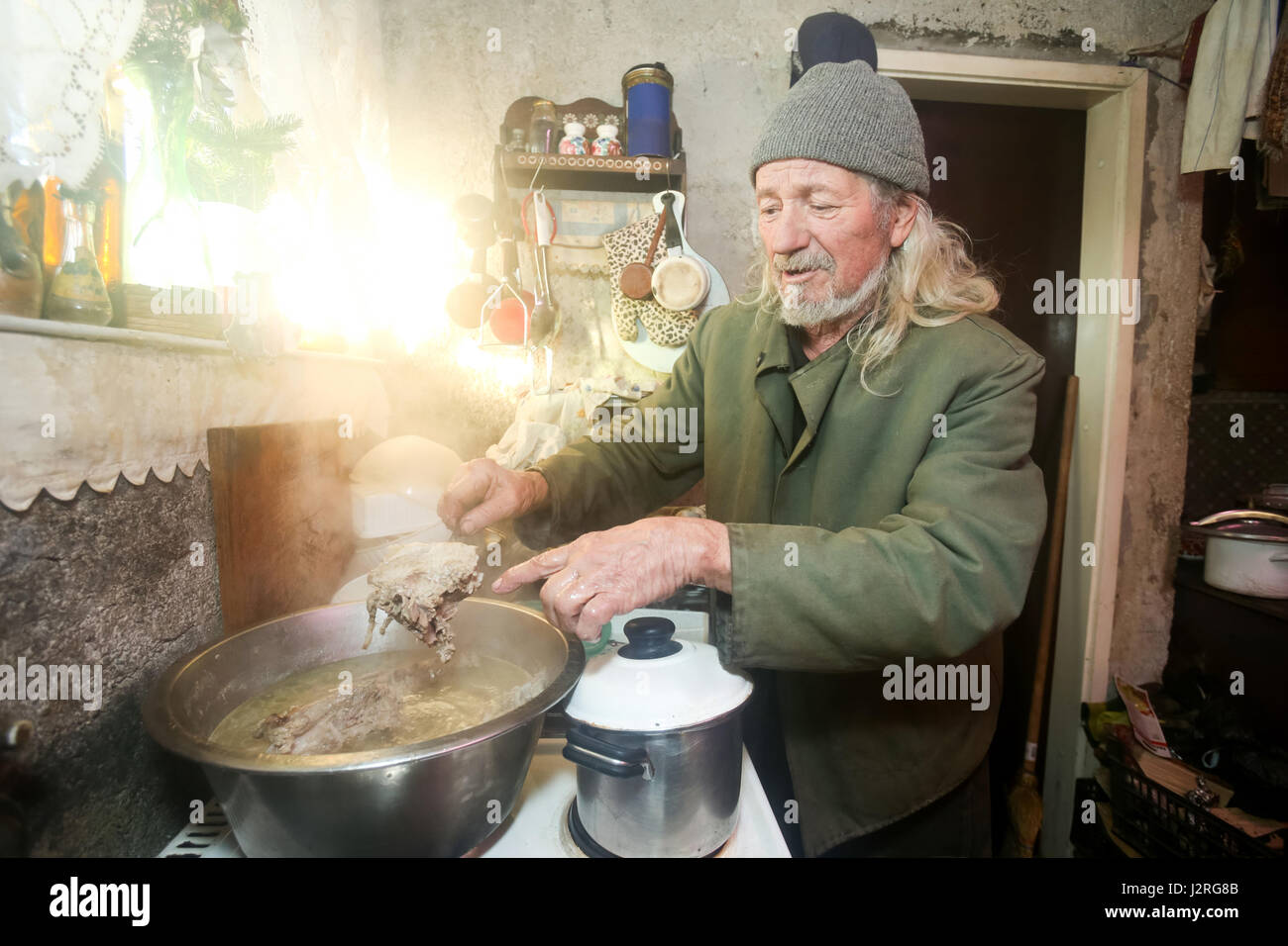 An old man boiling pork meat on the stove and showing a piece of meat on a fork. Stock Photo