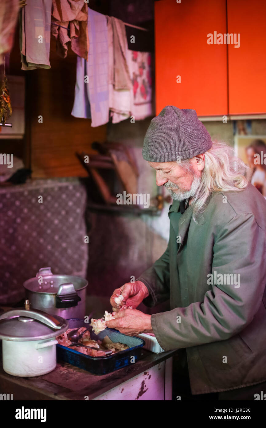 An old man eating pork meat after cooking it. - Stock Image