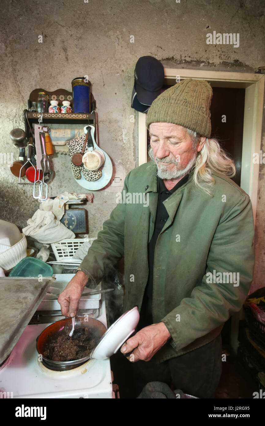 An old man cooking meat on stove in kitchen. - Stock Image