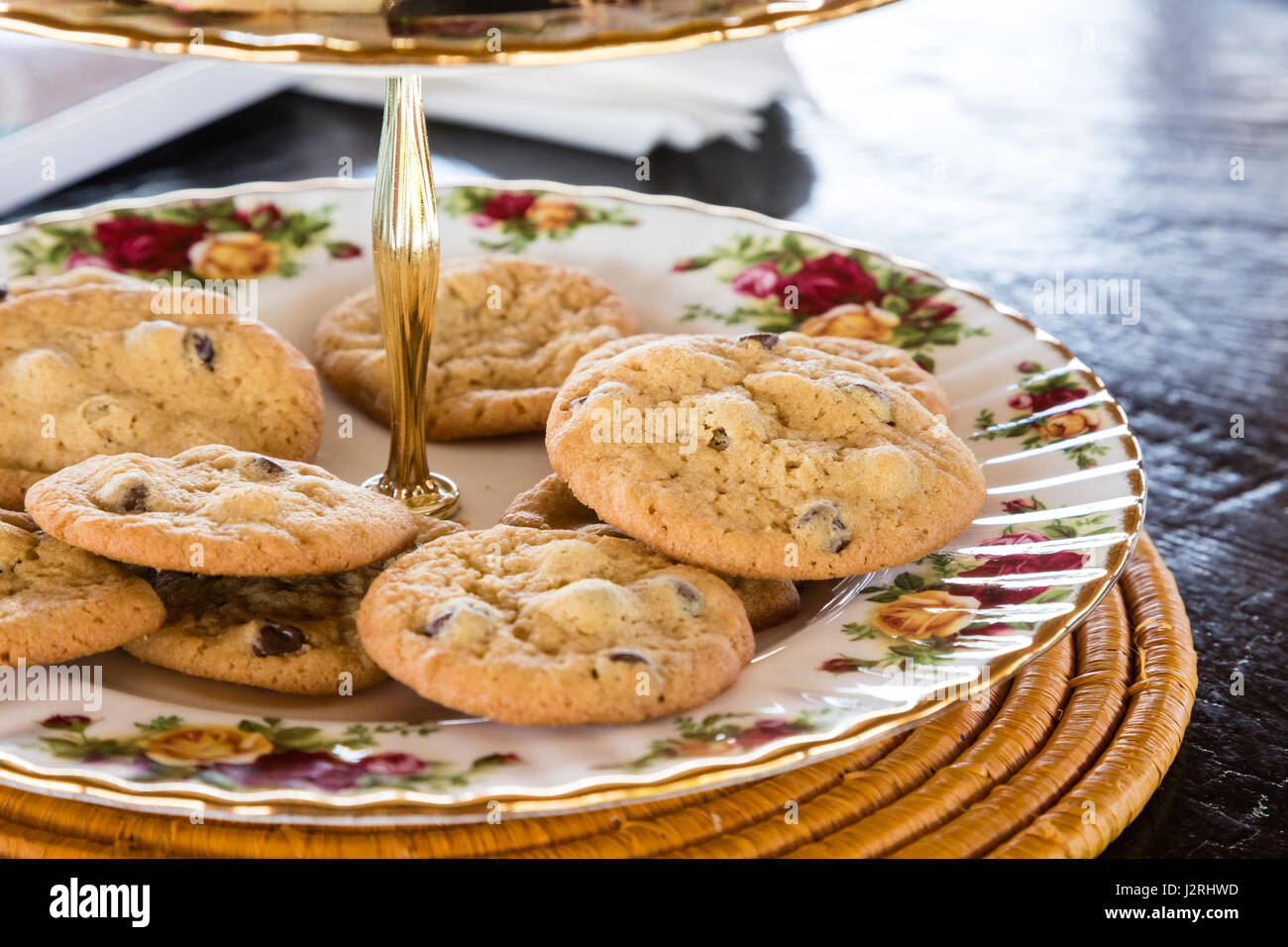 Homemade cookies on a fancy china tiered serving dish on the patio. - Stock Image