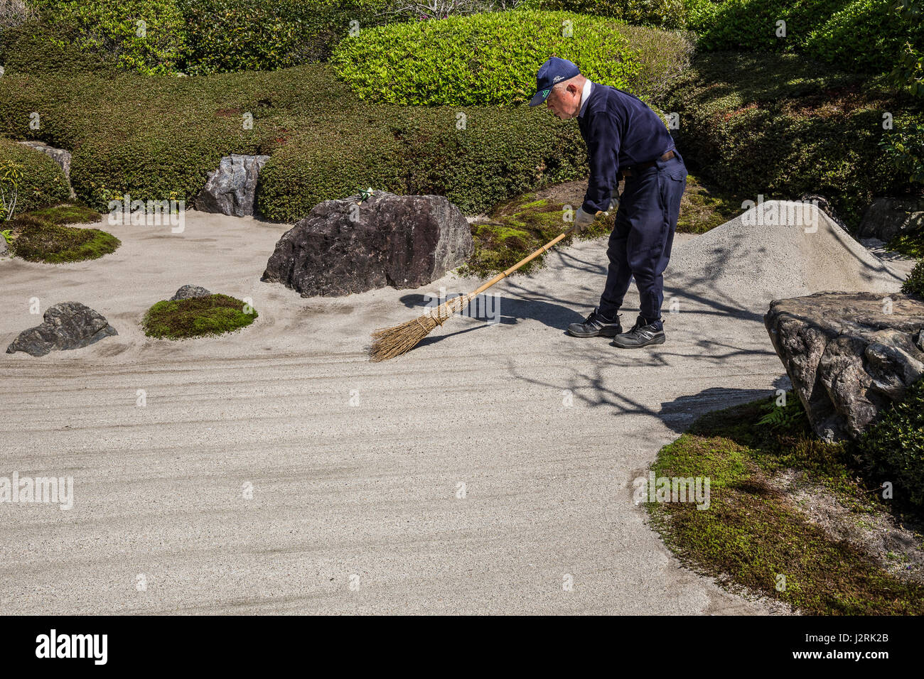 Meigetsuin Japanese Gardener - The karesansui zen garden of raked sand, rocks and plants at Meigetsuin Temple Garden - Stock Image