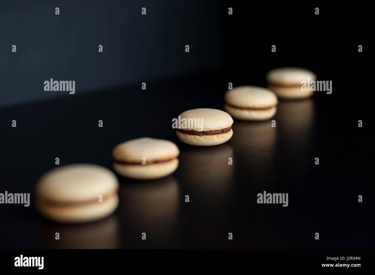 Macaroons with chocolate cream ordered in line - Stock Image