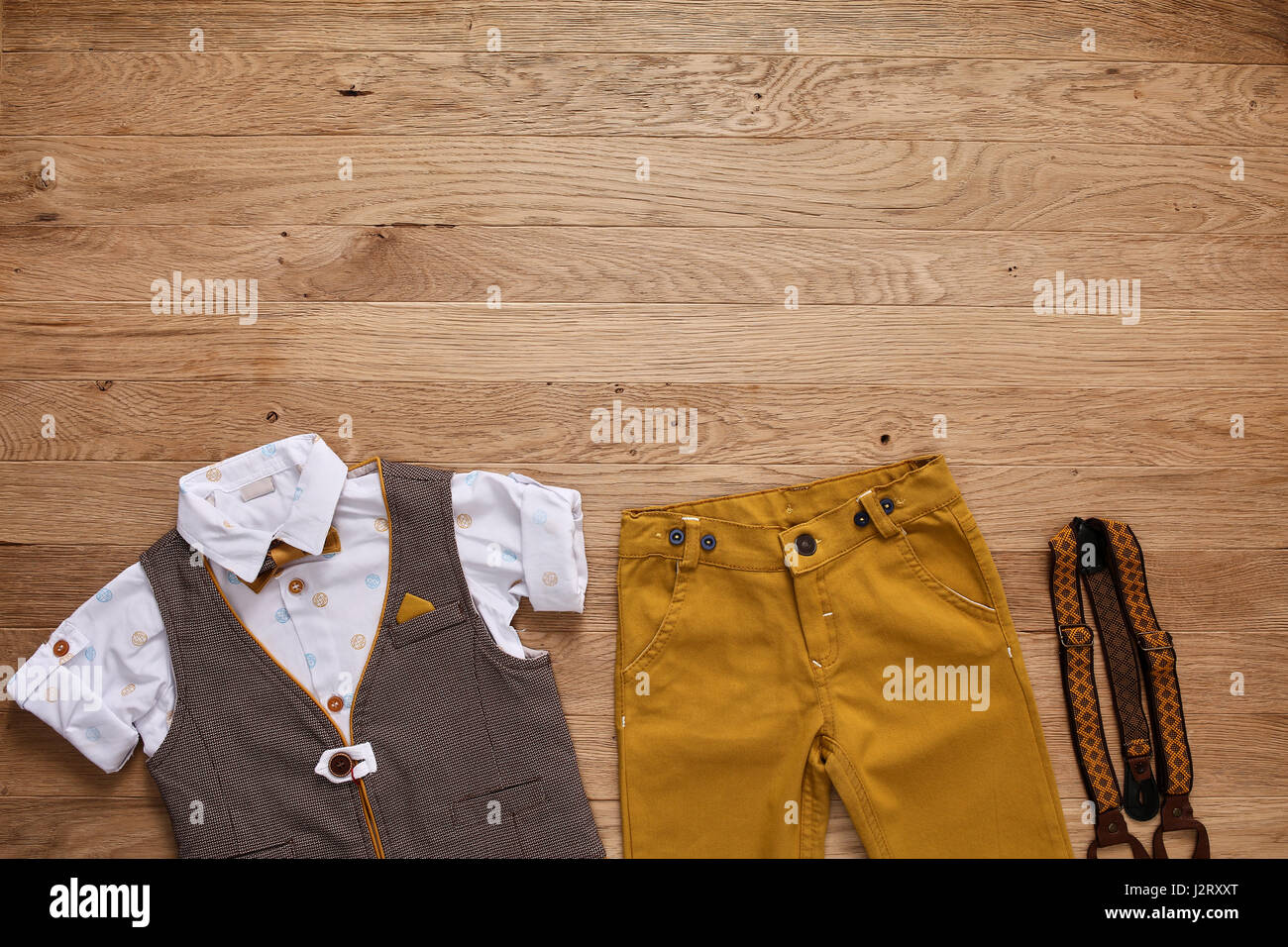b3342f5a280e8 Top view photo of the boy's clothes with accessories on the wooden  background. White shirt with print, brown vest, bowtie, brown pants and  suspenders.