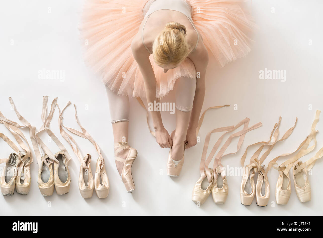 Female ballet dancer sits on the white floor and dresses a beige pointe shoe in the studio. She wears a light dance - Stock Image