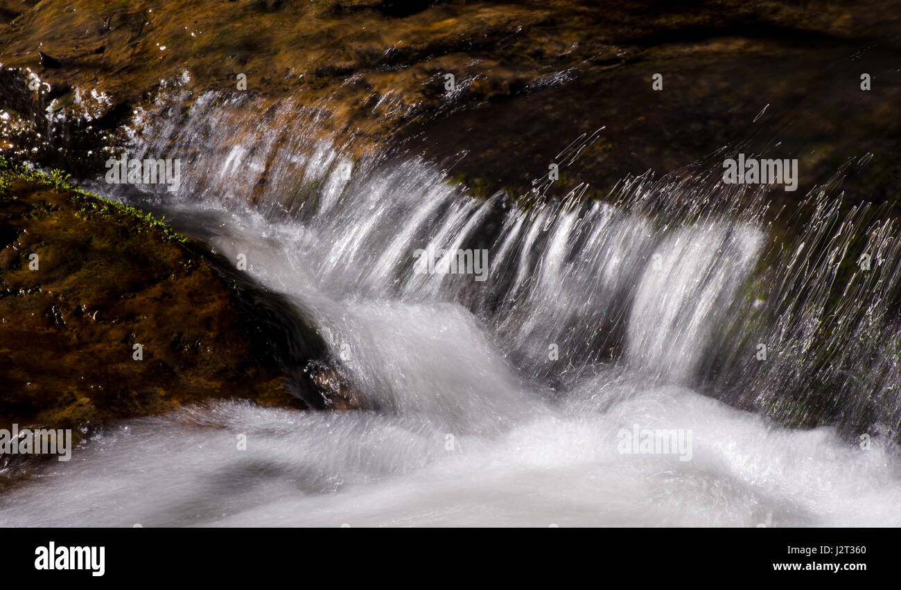 Clear water of a mountain stream runs swiftly over the rocks ahead of time, and forms a thin white of a water thread - Stock Image