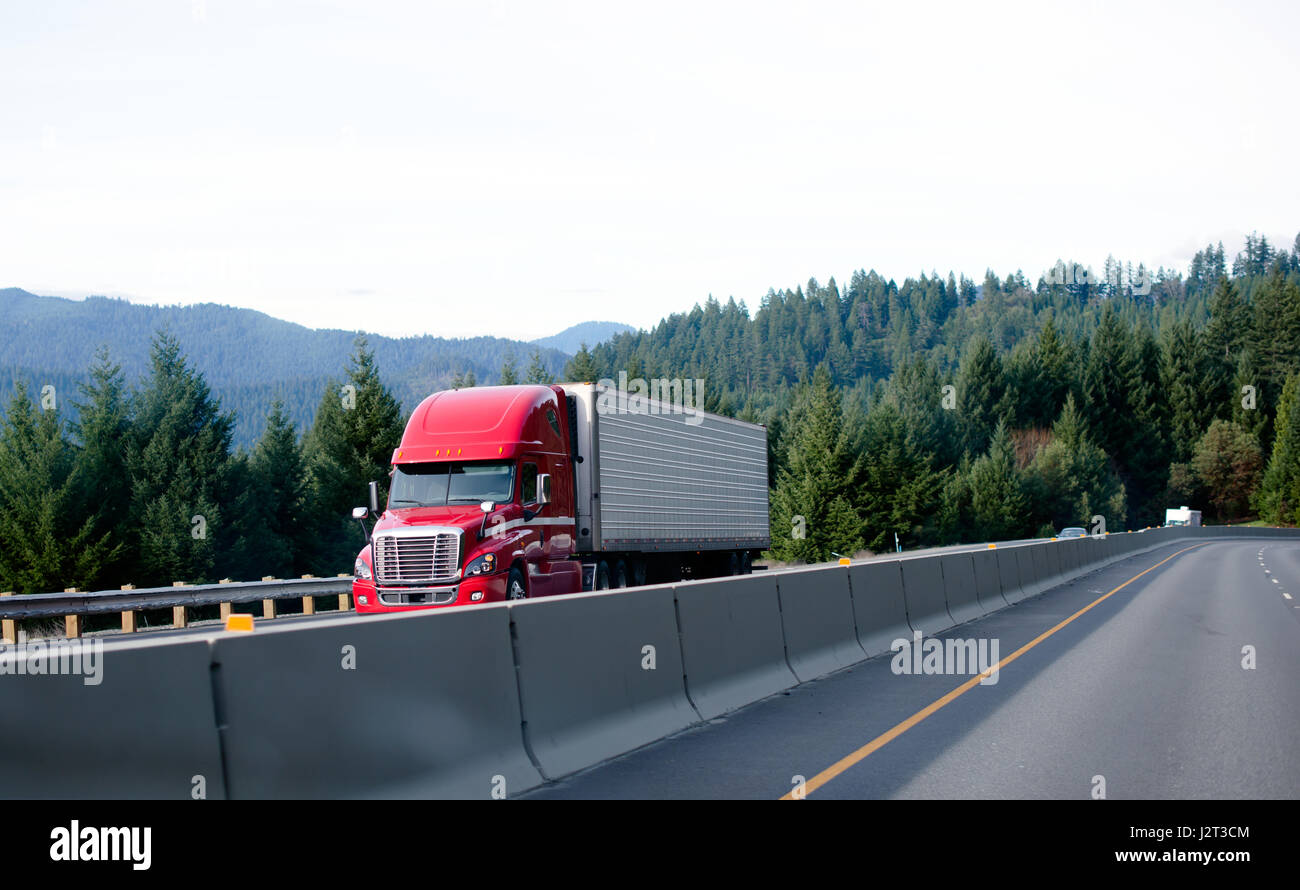 Red powerful modern professional semi-truck to haul a refrigerated trailer on the interstate highway with a concrete - Stock Image
