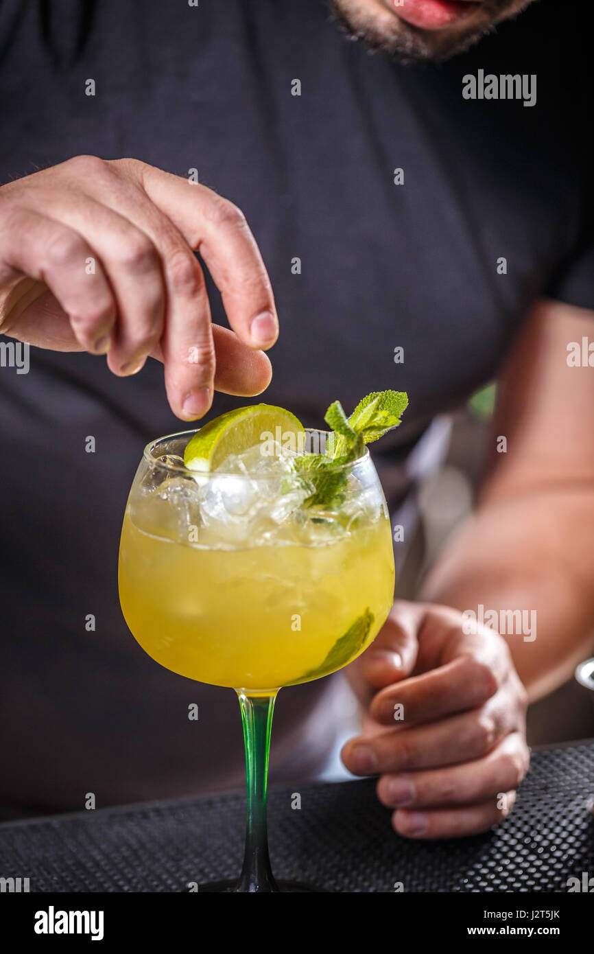 Bartender putting lime into glass, barman is decorating cocktail - Stock Image