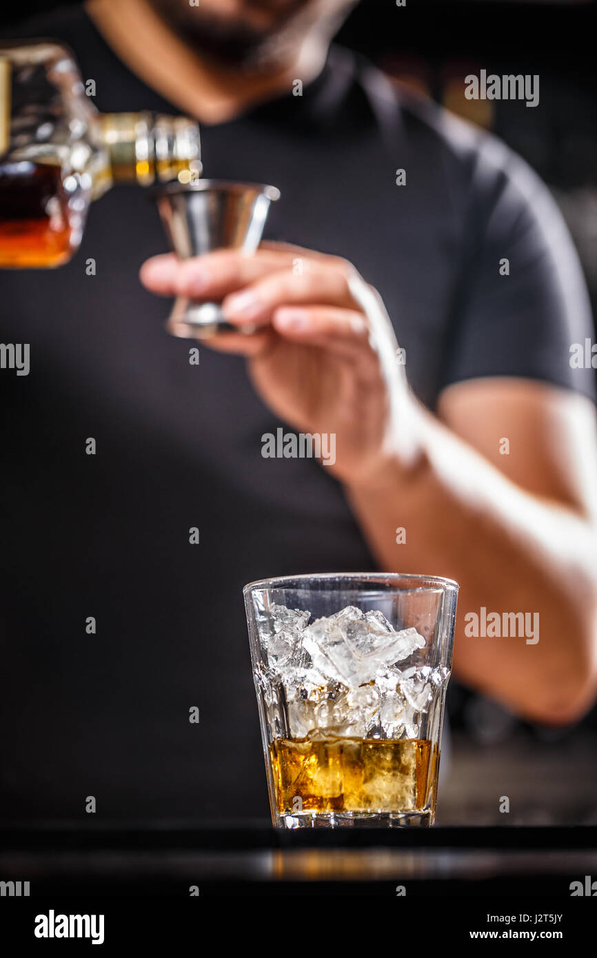 Bartender at work in bar pouring drink into measuring glass - Stock Image