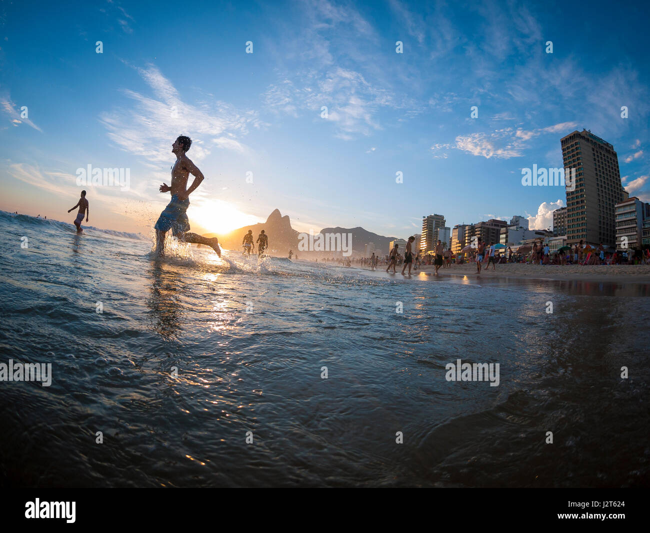 RIO DE JANEIRO - FEBRUARY 2, 2013: Silhouettes pass in front of the sunset on the shore of Ipanema Beach. - Stock Image