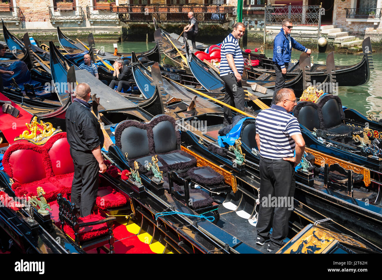 VENICE - APRIL 24, 2013: Venetian gondoliers work in the traditional Bacino Orseolo gondola parking lot behind the - Stock Image