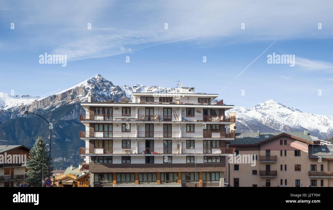 A hotel with a mountainous backdrop, Sauze d'Oulx ski resort, Turin, Piedmont, Italy - Stock Image