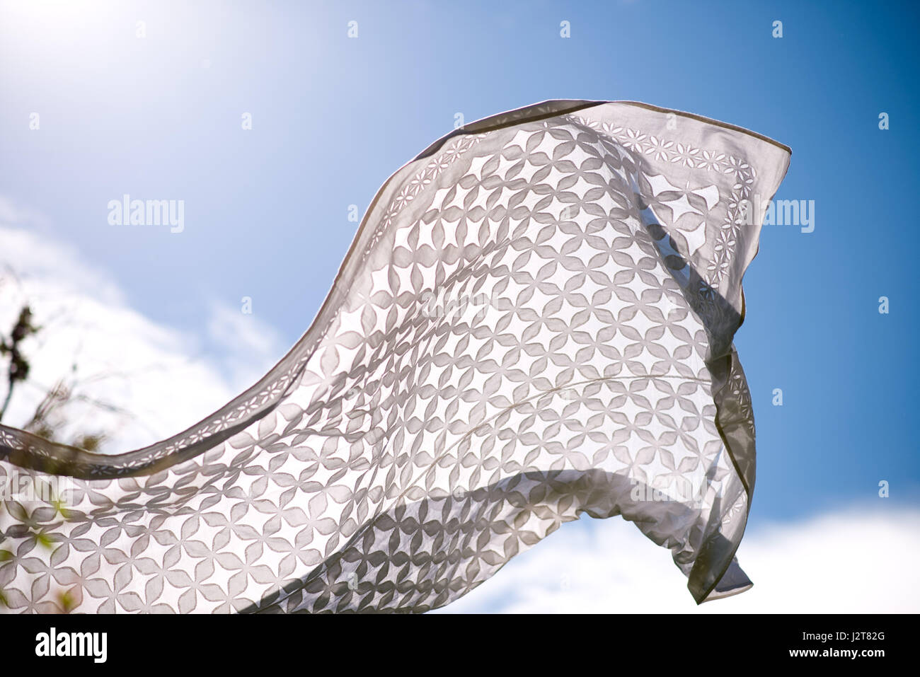 White table cloth/throw outside in the wind - Stock Image
