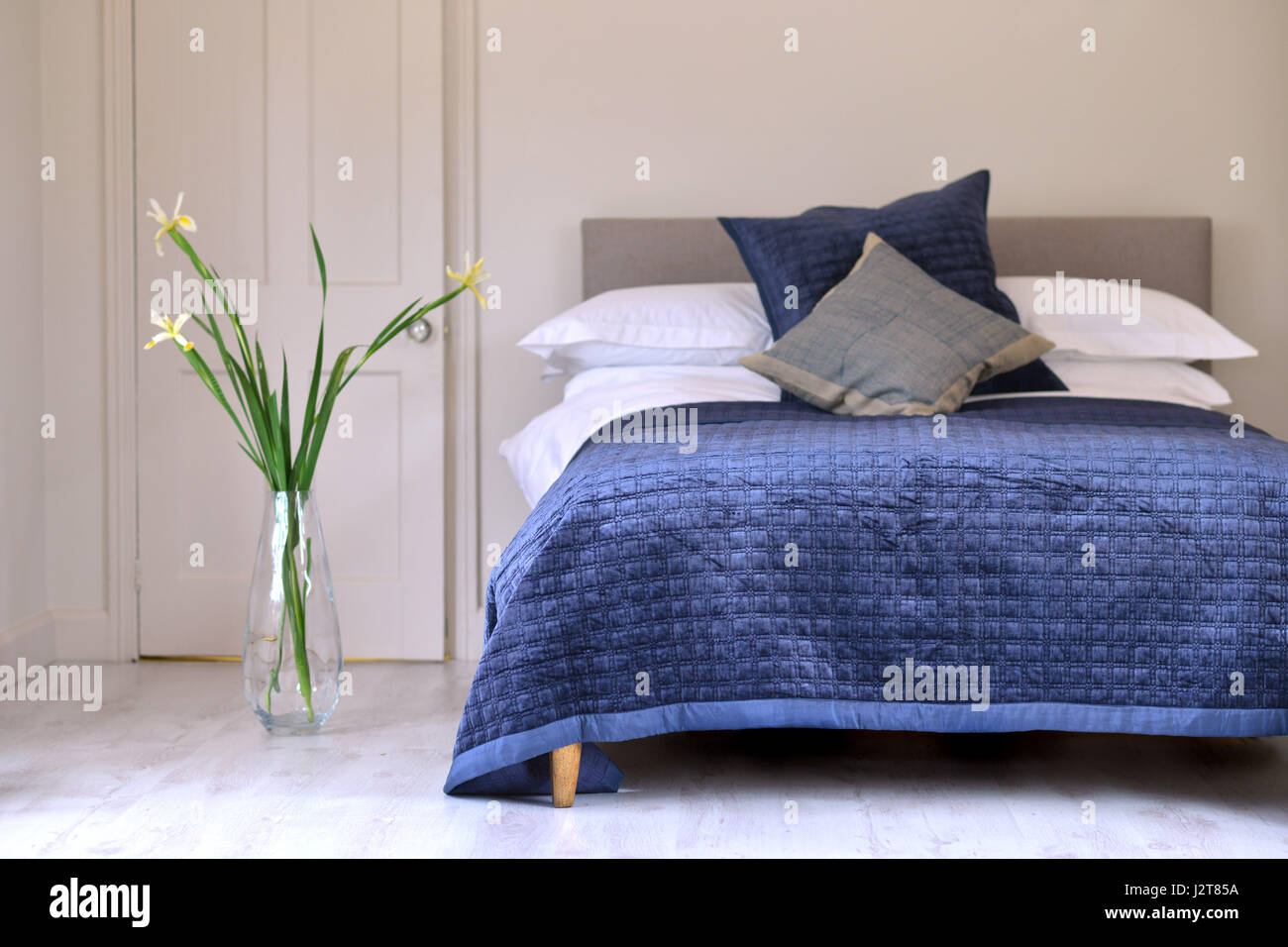Bedroom and bed with blue quilt - Stock Image