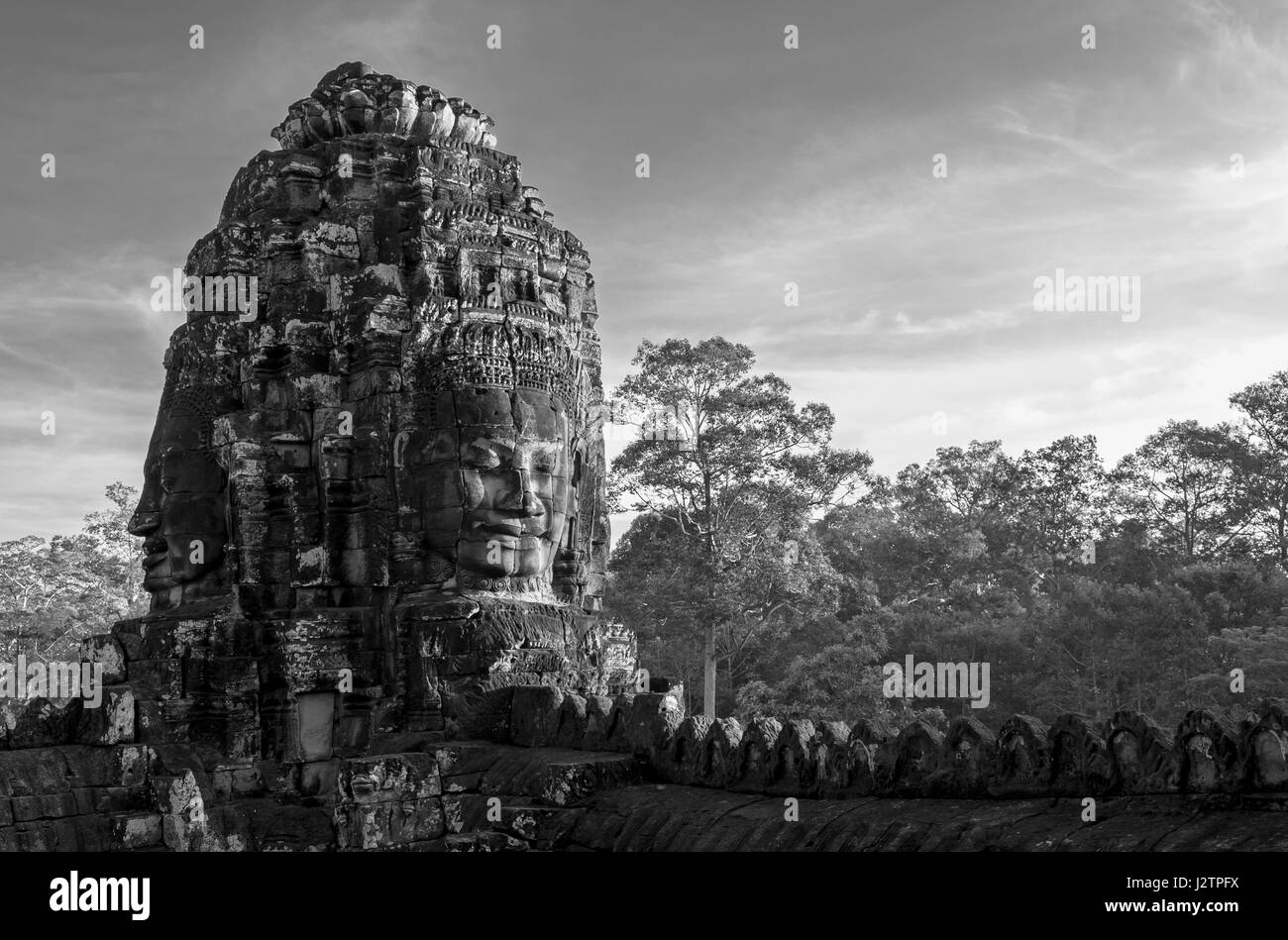 Black and white photograph of a smiling buddha head inside the bayon temple with the jungle in the background in angkor thom cambodia