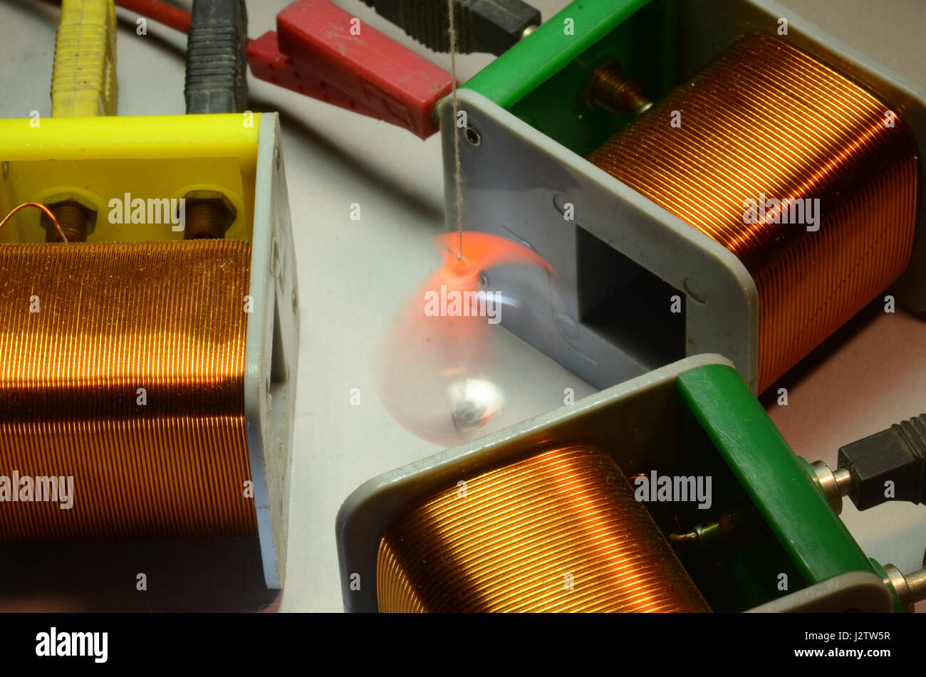 Demonstration of how a three-phase asynchronous motor works. The orange metal ring is influenced by the rotating - Stock Image
