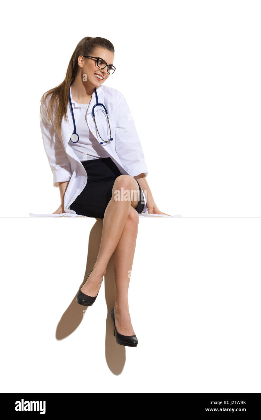 Cheerful young woman in glasses, white lab coat, black skirt and high heels sitting on a big white banner and looking - Stock Image
