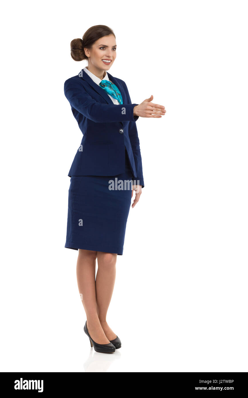 Young woman in blue formalwear and high heels, standing and giving hand for a handshake. Front side view. Full length - Stock Image