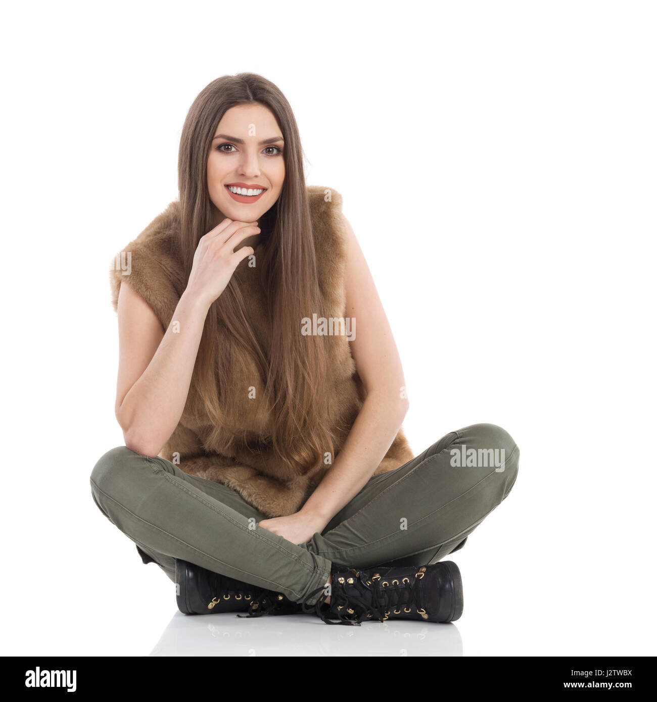Beautiful young woman in brown fur waistcoat and khaki pants sitting on floor with legs crossed, smiling and looking - Stock Image