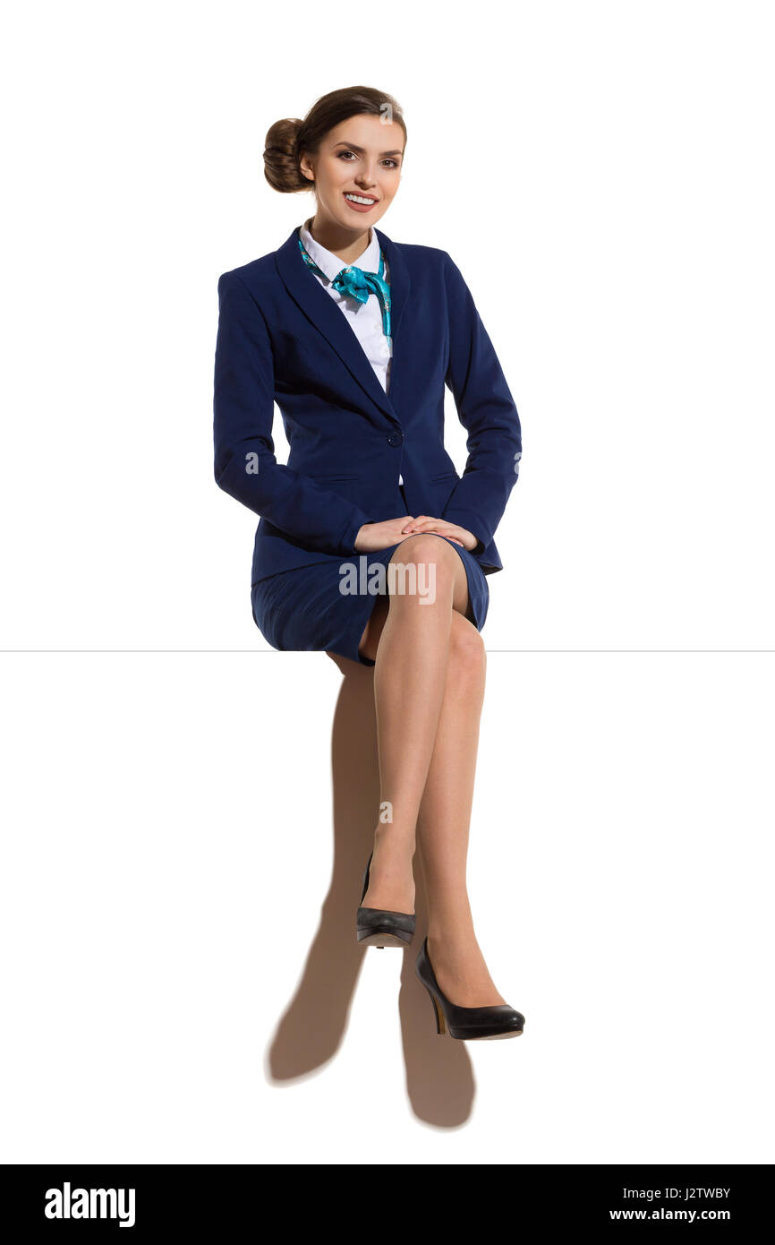Elegant woman in blue suit, skirt and black high heels, sitting on a top with legs crossed, smiling and looking - Stock Image