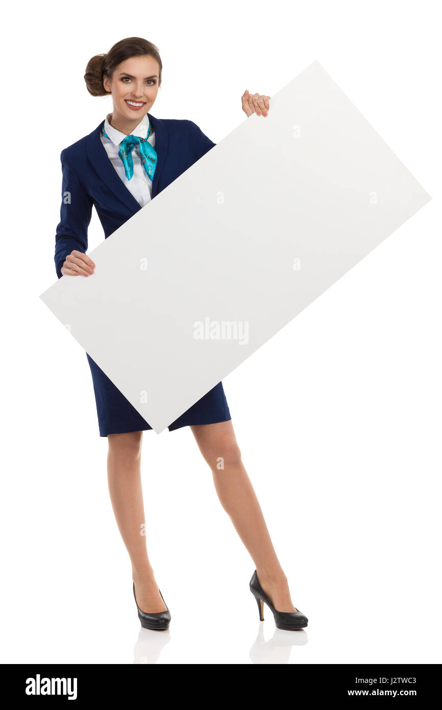 Young woman in blue formalwear and high heels, holding blank placard and smiling. Front view. Full length studio - Stock Image