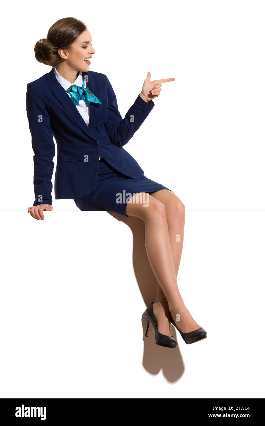 Elegant woman in blue suit, skirt and black high heels, sitting on a top with legs crossed, looking away, smiling - Stock Image