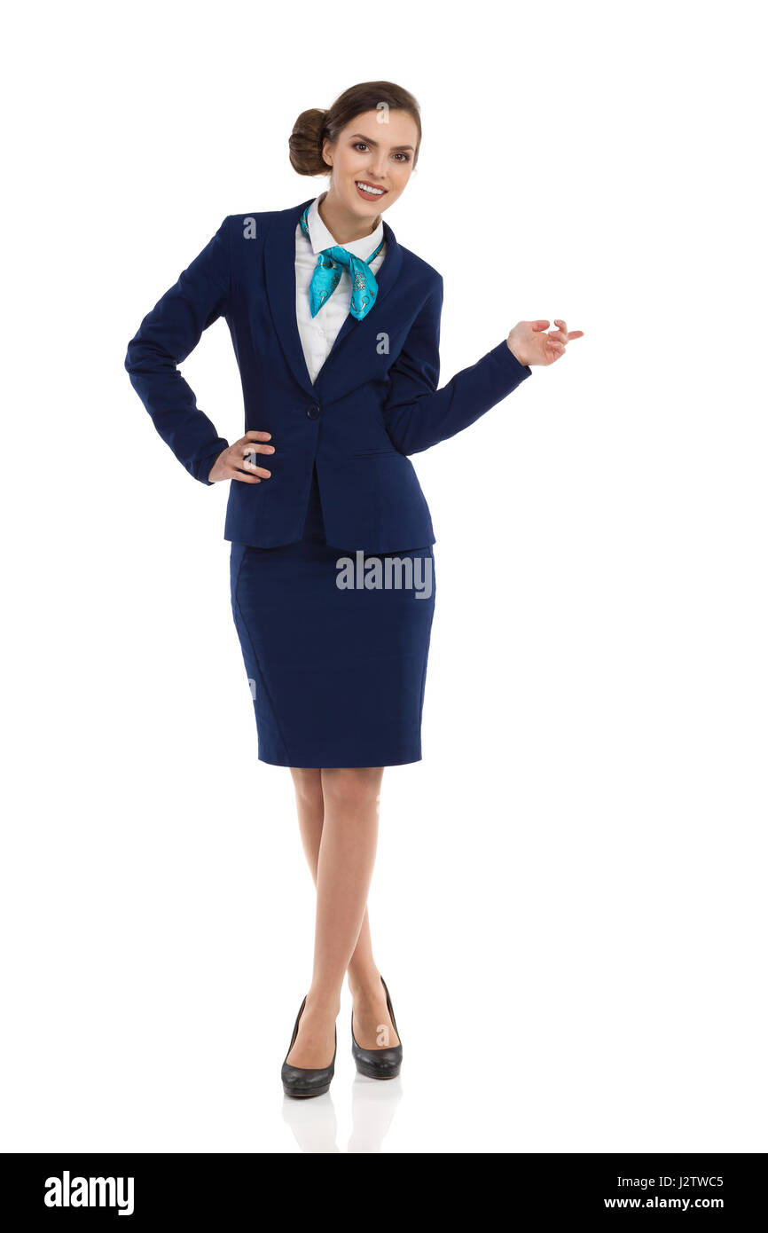 Young woman in blue formalwear and high heels, standing with hand on hip, looking at camera and pointing. Front - Stock Image