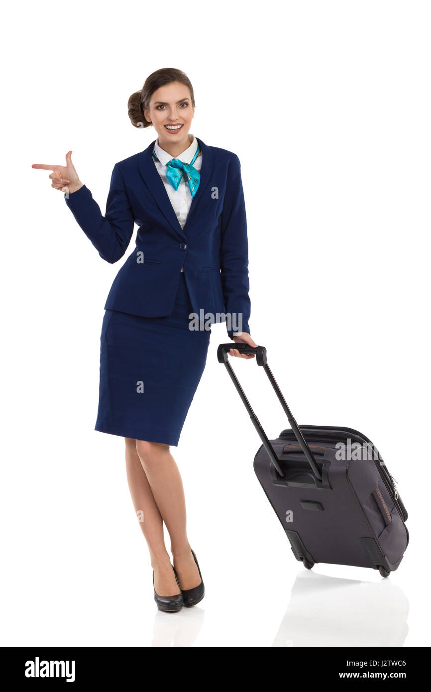 Smiling woman in blue suit and skirt walking with trolley bag and looking at camera. Full length studio shot isolated - Stock Image