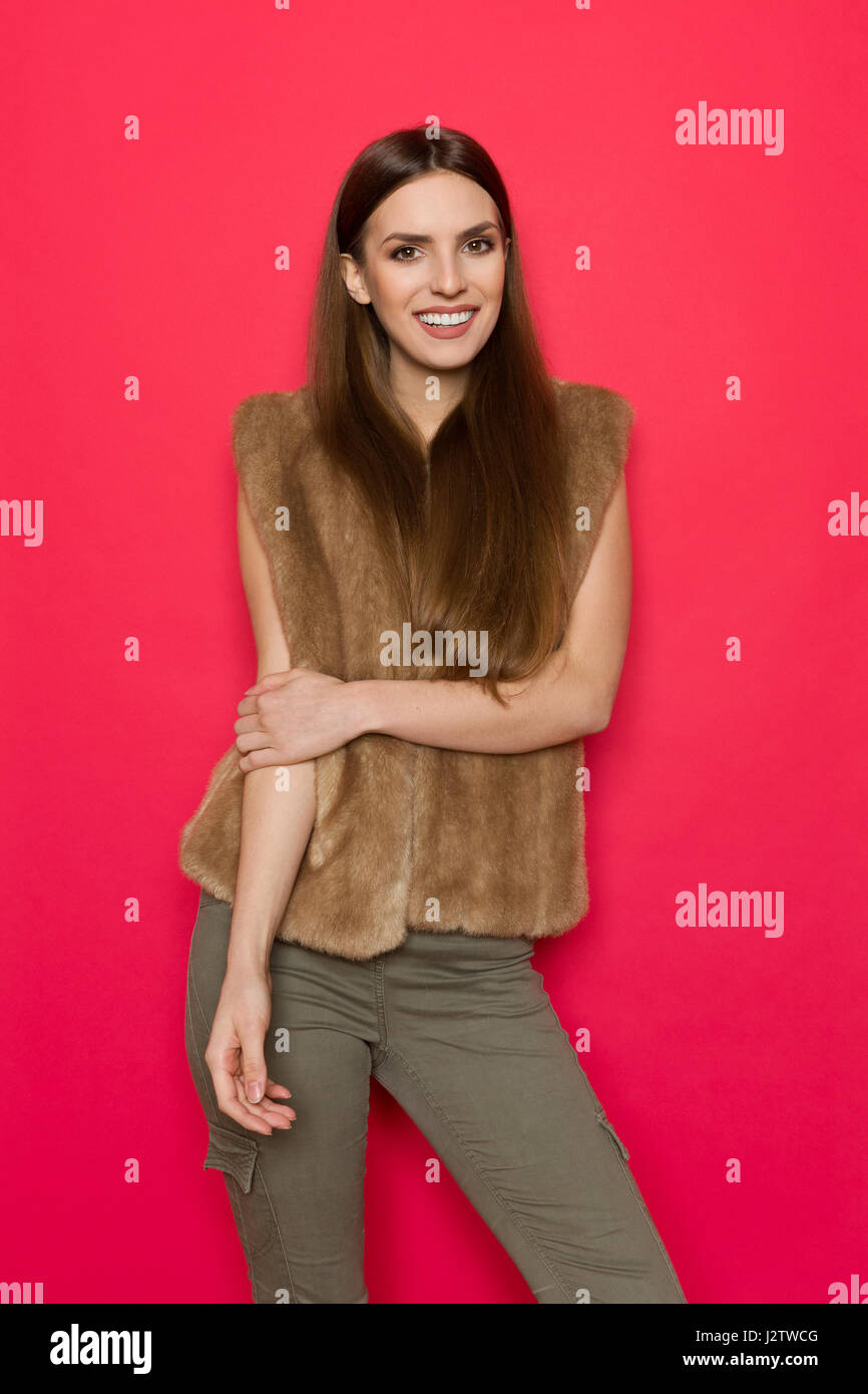 Smiling beautiful woman with long hair posing in brown fur vest and khaki pants. Three quarter length studio shot - Stock Image