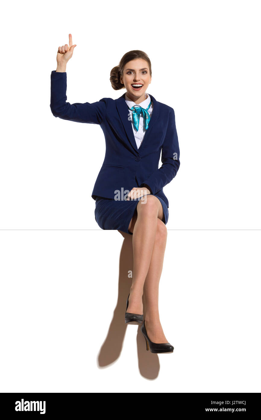 Smiling woman in blue suit and skirt, sitting on a top, looking at camera and pointing up. Full length studio shot. - Stock Image