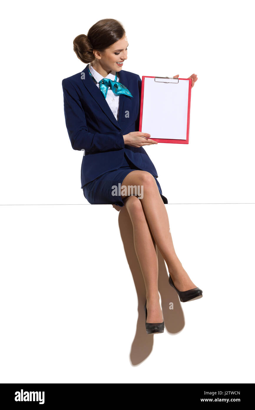 Elegant woman in blue suit, skirt and black high heels, sitting on a top with legs crossed, holding red clipboard - Stock Image