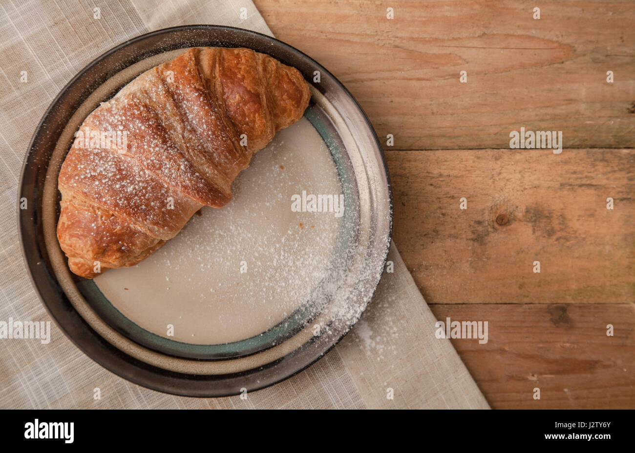 Top View of two fresh croissants dusted with icing sugar on a plate - Stock Image